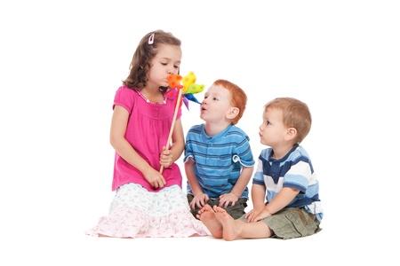 Trois enfants gonflant toy moulin à vent.  Isolé sur fond blanc.