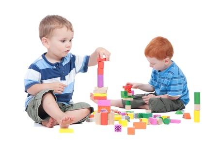 wood block: Preschooler boys playing with toy blocks.  Isolated on white.