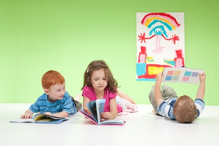 Three kids lying on floor reading books. On white and green. photo