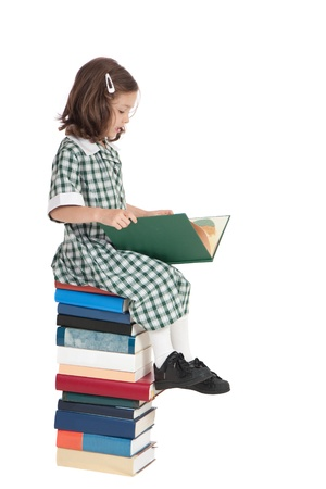 School girl in uniform sitting on stack of books reading. Isolated on white.