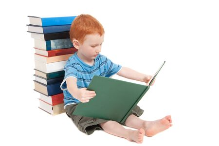 Young boy sitting on floor, leaning against pile of books, and reading Stock Photo - 8723943