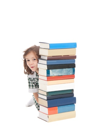 preparatory: School girl in uniform hiding behind pile of books. Isolated on white.