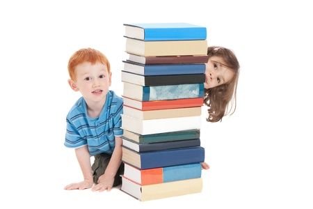 Two kids hiding behind stack of books. Isolated on white. Standard-Bild