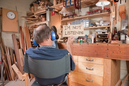 facing away: Man wearing ear muffs and holding sign Im not listening. Stock Photo