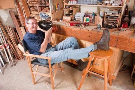 Senior man, écouter la radio en atelier