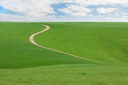 clean street: Winding dirt road going up green hill with blue cloudy sky Stock Photo