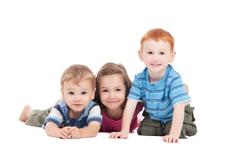 sibling: Three kids lying on floor. Isolated on white. Stock Photo