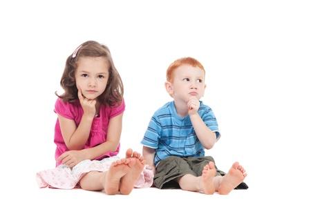 assis par terre: Deux enfants assis sur le plancher avec une expression de penser. Isol� sur blanc.
