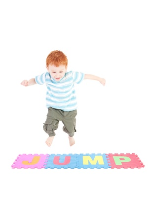 Young boy jumping over word jump. Isolated on white.