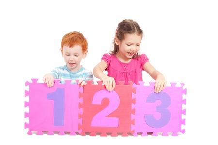 Deux enfants avec des tuiles numéros colorés. Isolé sur fond blanc.