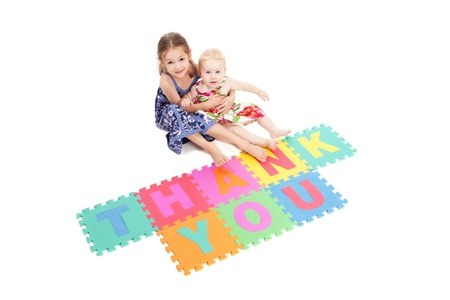 saying: Two girls saying thankyou with letter tiles. Isolated on white.