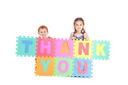 ni�os sosteniendo un cartel: Dos ni�os que firman gracias. Aislados en blanco.