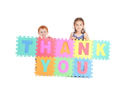 Two kids holding up sign saying thank you. Isolated on white. photo