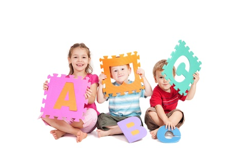 Three kids having fun learning with alphabet ABC letters. Isolated on white. photo