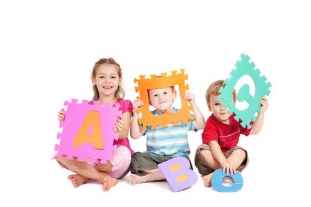 Trois enfants ayant l'apprentissage amusant avec alphabet lettres ABC. Isolé sur blanc.