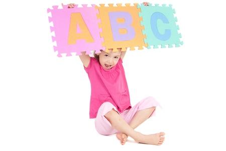 Niña con signo de abc de alfabeto por encima de su cabeza. Aislados en blanco.