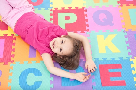 Smiling girl lying on alphabet tiles.