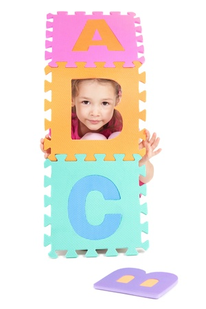 Girl playing with alphabet abc tiles. Isolated on white.