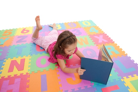 Girl reading book on colorful alphabet floor mat. Isolated on white. Stock Photo - 9080036