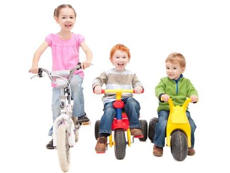Three kids riding bikes and trikes. Isolated on white.