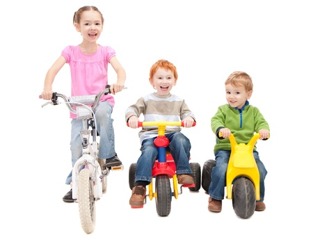 Three kids riding bikes and trikes. Isolated on white.