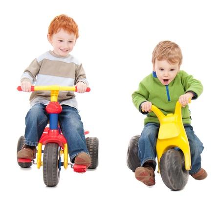 carritos de juguete: Ni�os montando trycycles. Aislados en blanco.