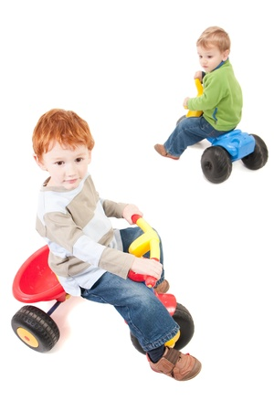 Boys riding kids tricycles. Isolated on white. Stock Photo