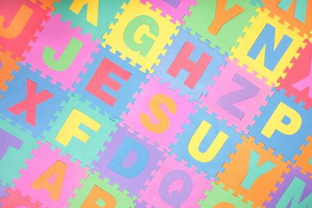 Colorful alphabet puzzle pieces and letter tiles background Stock Photo - 9334526