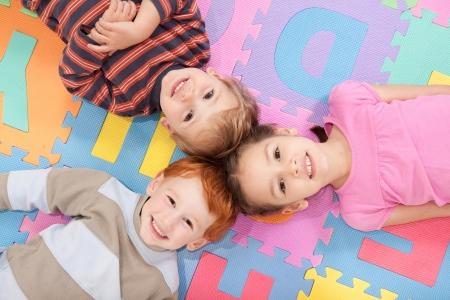 Three kids having fun lying on backs on alphabet mat. Standard-Bild