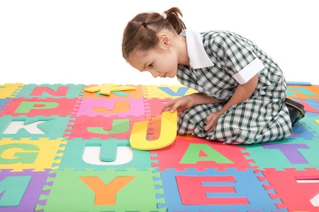 Girl in uniform finishing alphabet letter puzzle. Isolated on white. photo