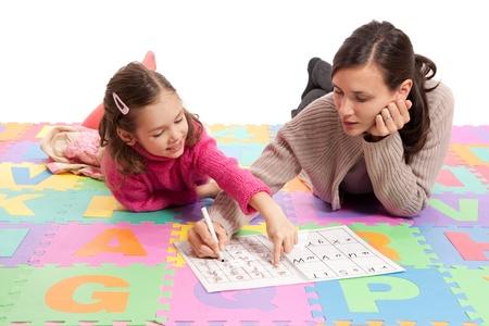 Girl learning handwriting practice from teacher. Isolated on white. Standard-Bild