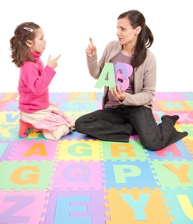 Fille d'apprentissage phonétique alphabet et les actions de l'enseignant. Isolé sur blanc Banque d'images