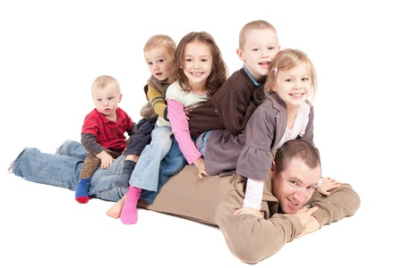 Children sitting on mans back on floor Stock Photo