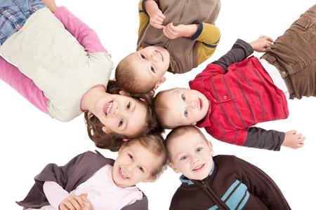 Group of happy kids lying on backs on isolated white floor.