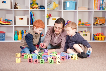 Mother playing blocks games with boys photo