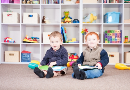 Two boys reading books in play room. Stock Photo