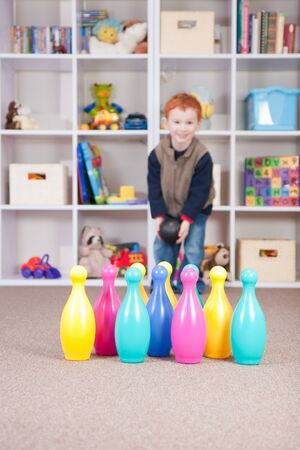 Boy playing ten pin bowling in play room photo
