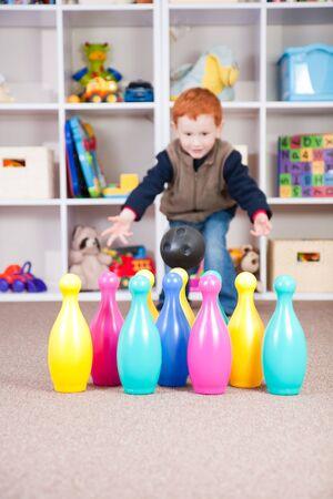 Boy playing ten pin bowling in play room photo