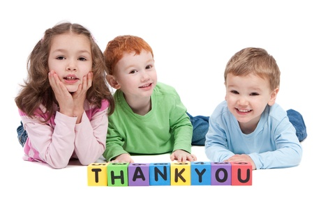 letter blocks: Three children lying with saying thankyou with kids letter blocks. Isolated on white. Stock Photo