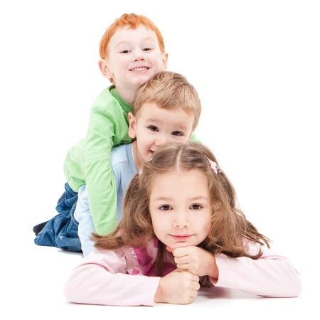 Three kids lying on top of each other. Isolated on white.