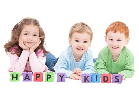 Three happy children with kids blocks. Isolated on white.