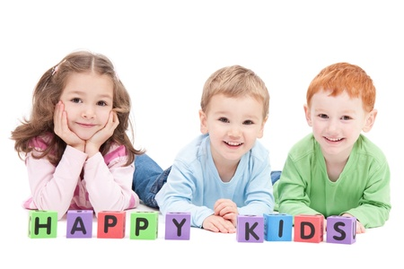 Three happy children with kids blocks. Isolated on white.