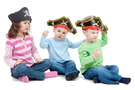 Three children playing in kids party pirate hats. Isolated on white. Stock Photo