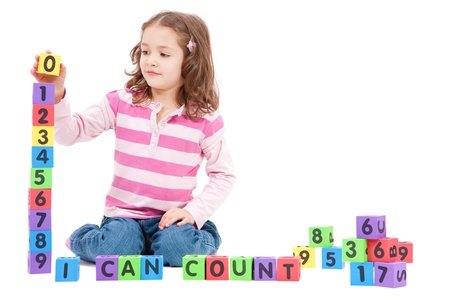 Girl counting numbers with blocks and saying I can count. Isolated on White