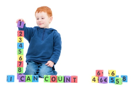 counting: Boy counting numbers with blocks and saying I can count. Isolated on White Stock Photo