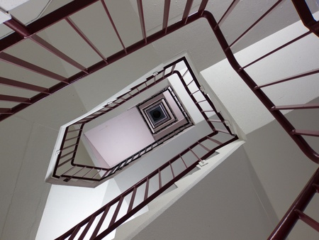 Looking up winding stairwell with geometric pattern photo