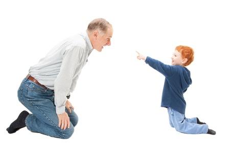 inginocchiarsi: Boy bambino si diverte con il nonno. Isolato su bianco.