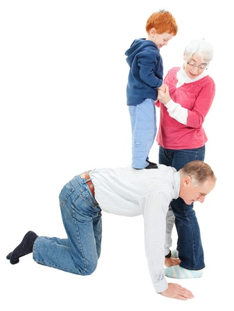 Grandmother and grandfather having fun playing with boy grandchild. Isolated on white.