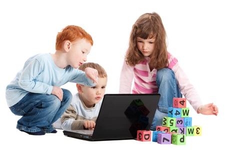 Enfants apprentissage de la lecture avec des blocs et ordinateur portable. Isolé sur blanc