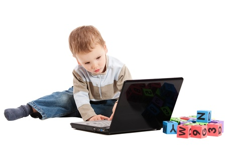 Preschooler boy learning to read using kids blocks and notebook computer. Isolated on white. photo